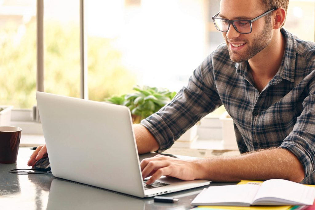 Man learning English online using a laptop